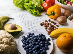 An image shows a variety of healthy foods spread on a table with a number of meal plans. The Mayo Clinic Diet is largely effective because it helps individuals creating a dietary plan with healthy meaning planning.