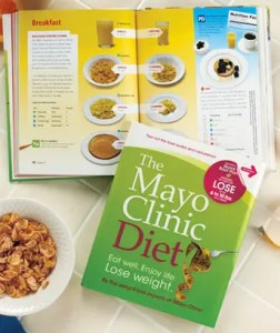 An image shows the Mayo Clinic Diet Book and accompanying recipe book with a bowl of cereal next to them.