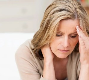 An image shows a distressed woman with one hand on her head and another on her neck. This image represents the idea of the mind-body connection which is an importance concept in Mindfulness-Based Stress Reduction (MBSR).