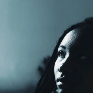 The face of a young African-American woman is shown as she looks upwards towards light entering her home. This picture is featured in Balanced Achievement's article on morning questions.