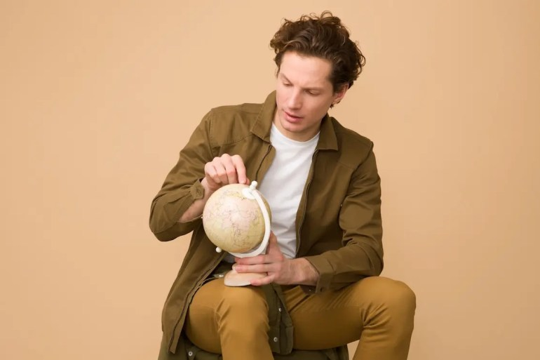 An image shows a well dressed man sitting on a stool as he points his finger at a globe he is holding. This picture serves as the featured image for Balanced Achievement's article 'Integrity and Intelligent Effort: The Foundational Elements Needed to Change The World.