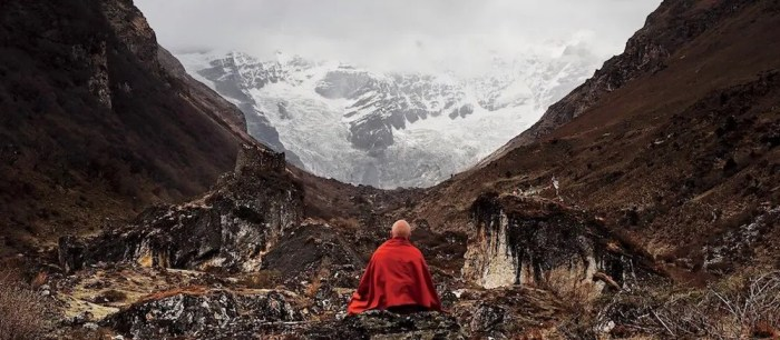 An image shows the celebrated Buddhist monk Matthieu Richard sitting in a meditation posture high in the Himalayan Mountains.