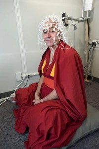 An image shows the iconic Buddhist monk Matthieu Ricard with brain monitoring wires strapped to his head before he undergoes a test aimed at studying the mental effects that come from meditation practice.