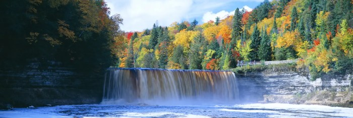 An image shows a picturesque scene of a waterfall surrounded by fall foliage. This picture is featured in Balanced Achievement's article on the wisdom of famous naturalists.