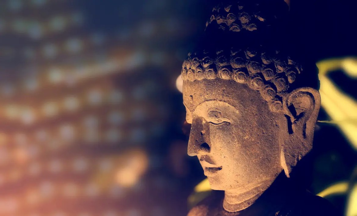 An image shows an ancient Buddha statue situated next to auspicious lights. This picture served as the featured image for Balanced Achievement's article '20 Authentic Buddha Quotes from the Dhammapada.'