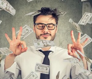 An image shows a businessman in glasses meditating under money raining down and represents the idea that we can change our financial beliefs with the help of a mindful money management plan.