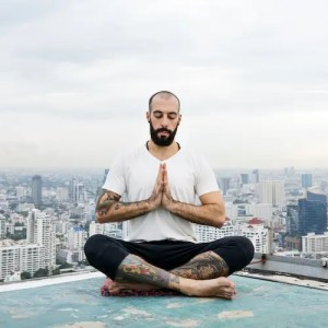 An image shows a modern man sitting on top of a tall building with a city skyline behind him. This picture is featured in Balanced Achievement's article about mindful money to introduce the practice of mindfulness in modern times.