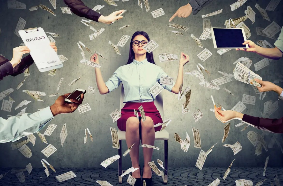 An image shows a young business woman meditating as money rains down with various arms reaching out, with various financial and social temptations, from the side of the image. The picture serves as the featured image of Balanced Achievement's article titled 'Mindful Money: Achieving Financial Freedom with Clarity and Contentment'.