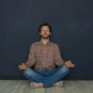 An image shows a casually-dressed man sitting on a wooden floor meditating. This picture represents the idea that we can go beyond the limiting relationship between natural selection and life-satisfaction with understanding and contentment.
