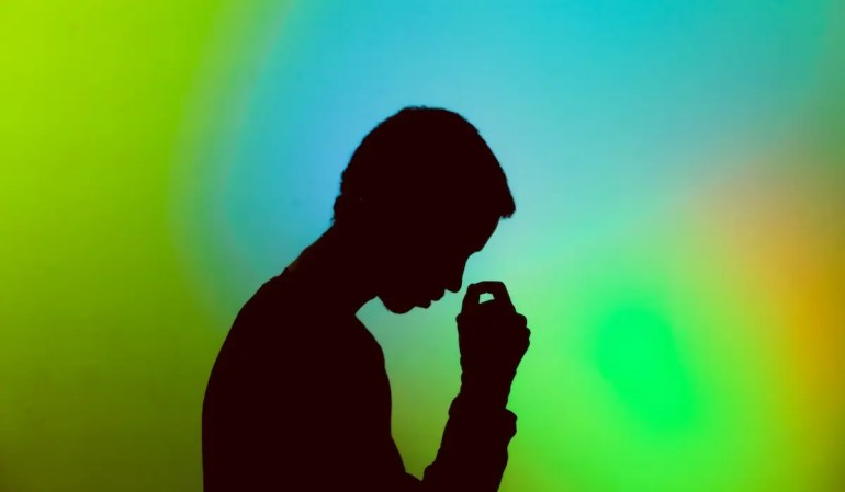 An image shows a black silhouette of man against a blue and green backdrop. The man is looking down in a state of discontentment and is about to put his hand on his head. This picture serves as the featured image for Balanced Achievement's article on natural selection and life-satisfaction.