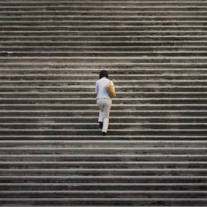An image shows a middle aged woman walking up what seems to be an unending set of stairs. This picture represents the psychological concept of the Hedonic Treadmill in Balanced Achievement's article on natural selection and life-satisfaction.