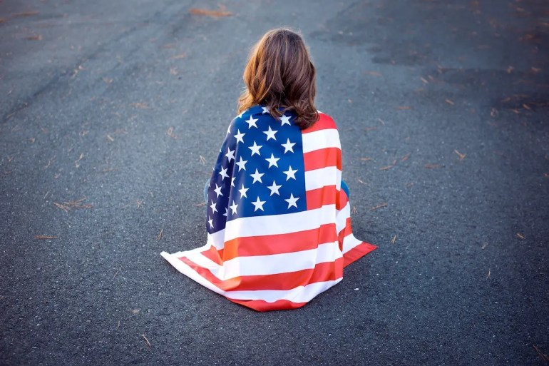 An image shows the black of a young woman sitting on the ground in a meditation posture with an American flag draped around her back. This picture serves as the featured image for Part II of Balanced Achievement's article '6 Spiritual Teachers on America's Divisive Political Climate'.