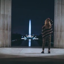 An image shows a woman looking at the Washington Monument while scratching her head in a state of bewilderment. This picture is featured in Balanced Achievement's article '6 Spiritual Teachers on America's Divisive Political Climate — Part II'.