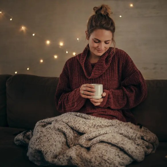 An image shows a young woman positively thinking with a blanket wrapped around her and a cup of warm tea. This picture is the featured image in Balanced Achievement's article on 5 nighttime questions that encourage happiness and growth.