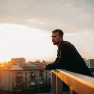 A young man is shown pondering on a terrace of his apartment against the backdrop of a cityscape at sunset.