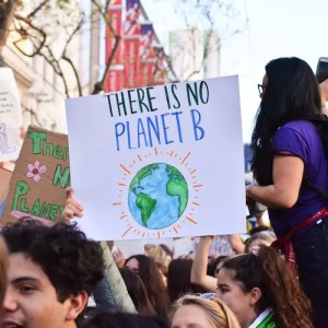 An image, which is used in Balanced Achievement's article examining 20 inspirational Environment Day quotes, shows a climate change protest unfolding with a sign that reads 'There Is No Planet B.'.