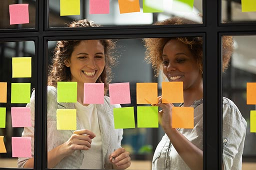 People looking at post it notes on a glass wall
