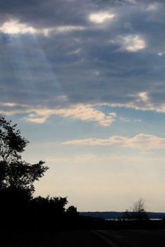 sun rays through cloudy blue sky