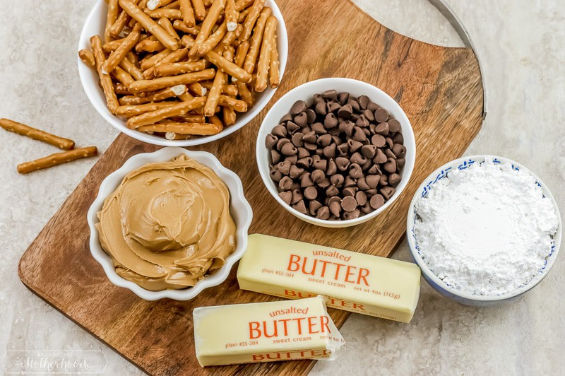 pretzels, chocolate chips, peanut butter, powdered sugar, butter ingredients on cutting board