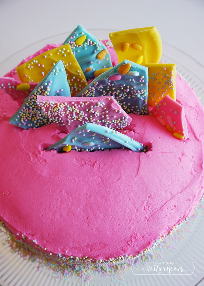 spring cake with pink, teal and yellow chocolate on top