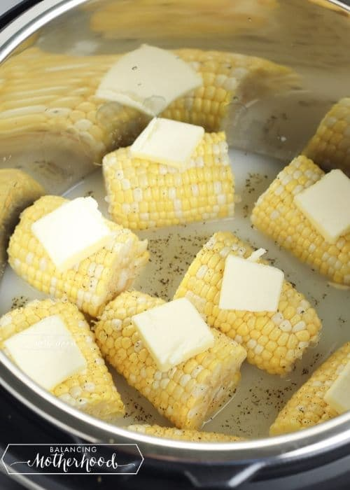 corn on the cob pieces with pats of butter on top in instant pot