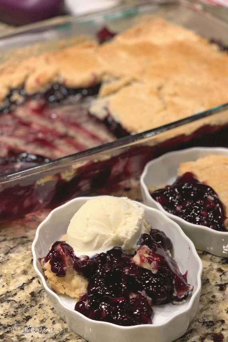 blueberry dump cake piece with ice cream on top