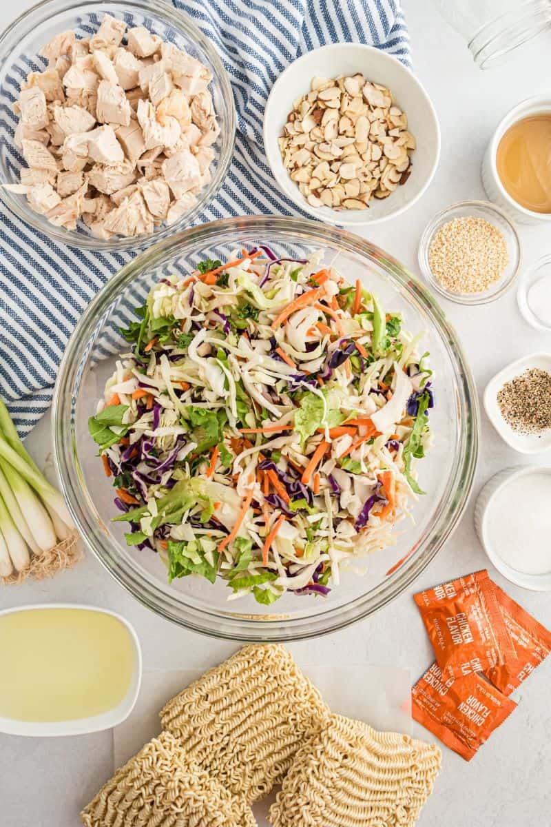 bowls of ingredients: cabbage, chopped chicken, almonds and dressing