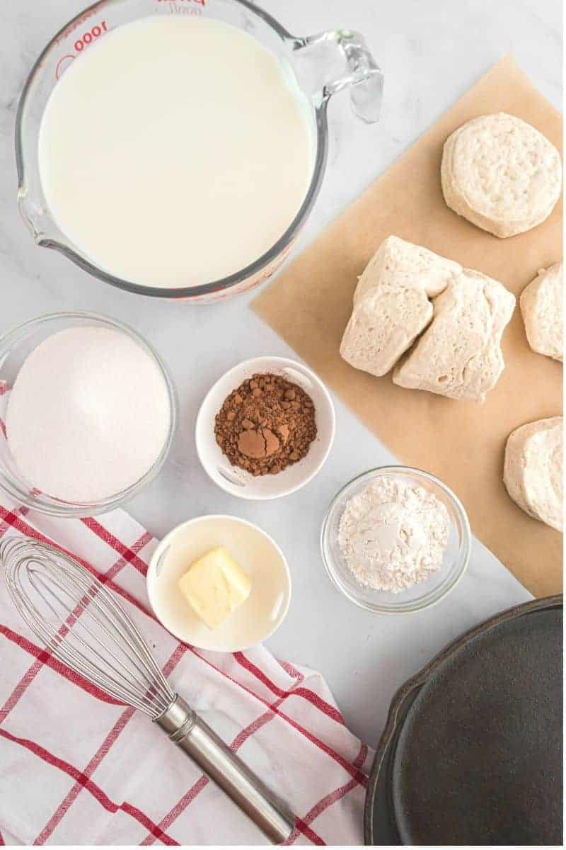 milk, cocoa, sugar, flour, milk and biscuits on counter