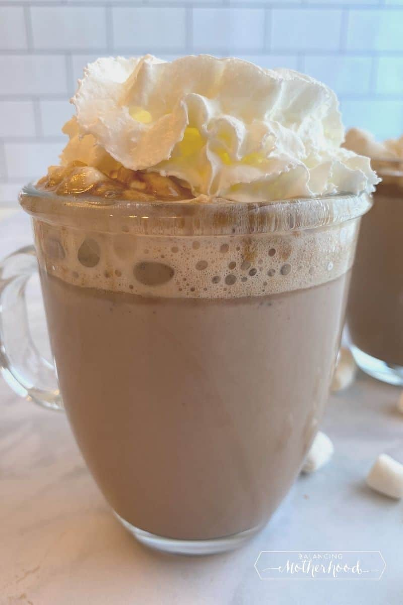 clear mug with hot chocolate and whipped cream on top