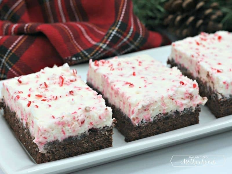 three brownies with candy cane buttercream frosting on a plate