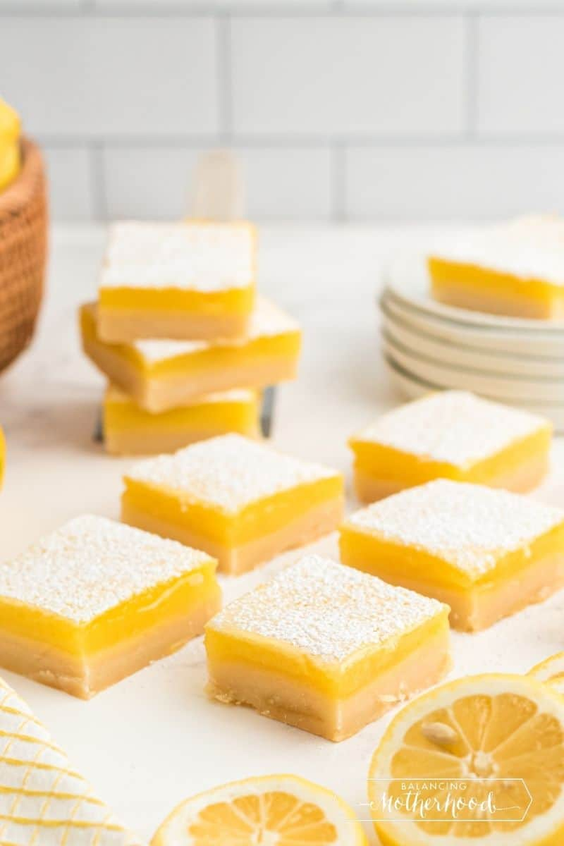 five lemon bars on table with lemon cut in half, three stacked in background