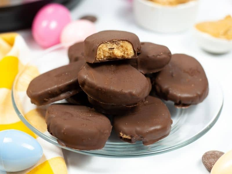 stack of peanut butter eggs on clear plate with easter eggs in background