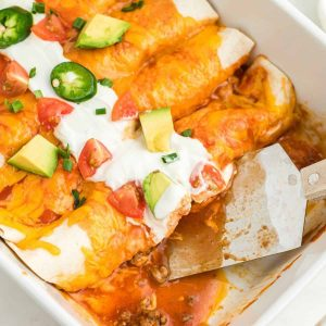 flour tortillas rolled and topped with red sauce, melted cheese and sour cream in baking dish