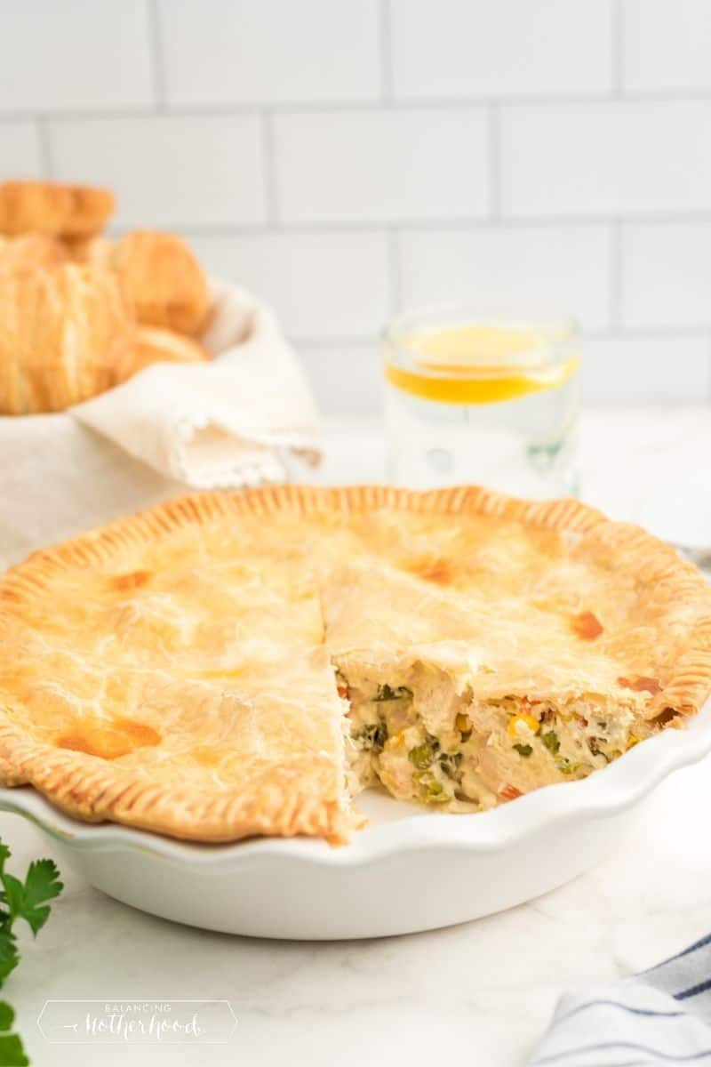 pot pie in white pie dish with slice removed. You can see chicken and green vegetables inside