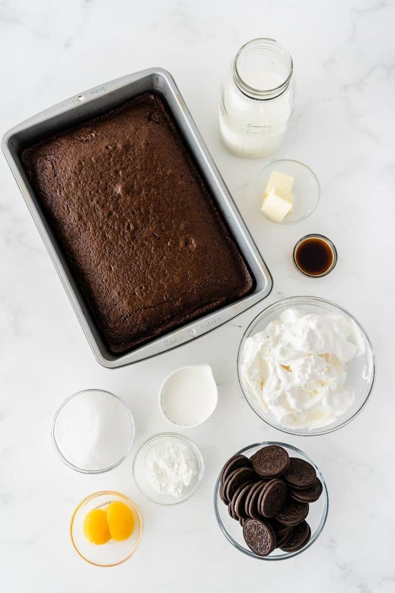 cake pan with chocolate cake, butter, milk, vanilla, whipped cream, oreo cookies, salt, cornstarch, eggs and oil on a table.