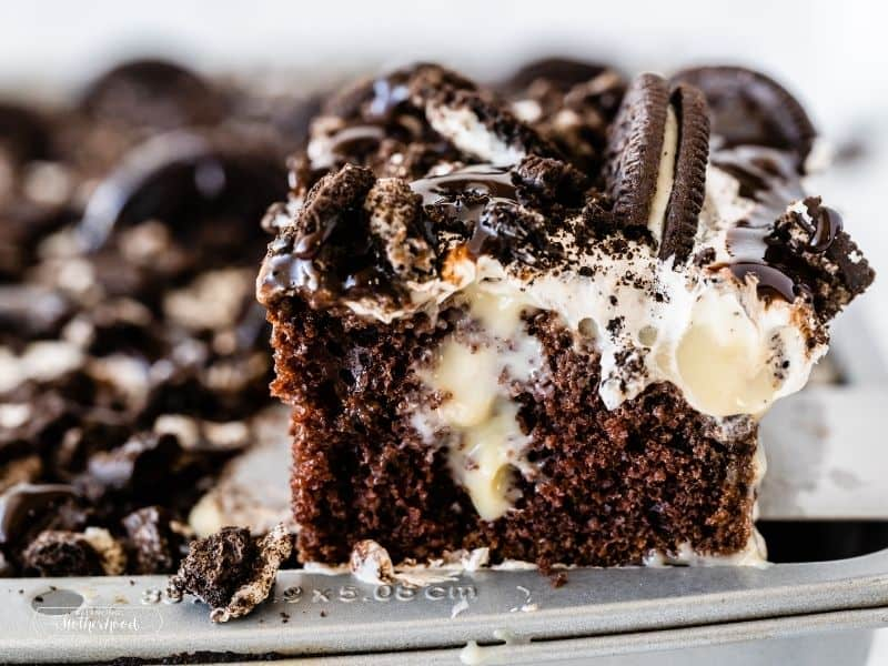 chocolate cake slice coming out of a ban with pudding and cream frosting topped with chocolate syrup and Oreo cookie pieces