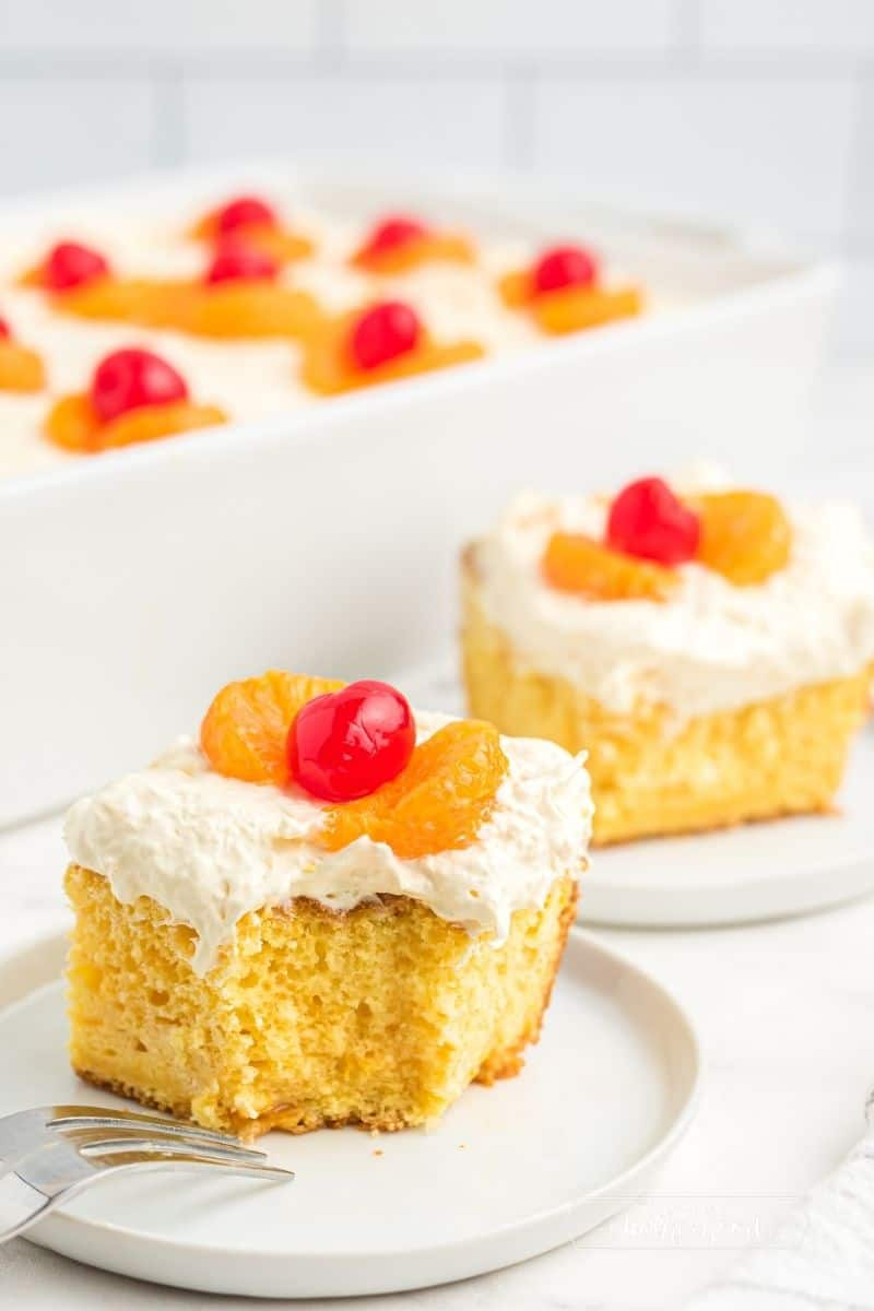 two slices of cake with mandarin oranges and a cherry on top