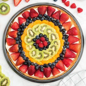 fruit pizza with slice cut out: strawberries, blueberries, mandarin oranges, kiwi, blueberries, raspberries in the middle.