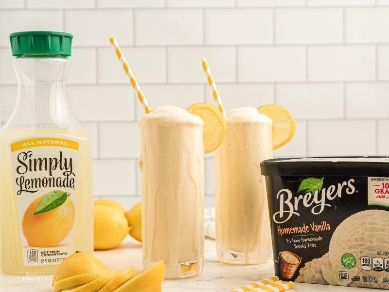 Simply Lemonade jar with two glasses of frosted lemonade with whipped cream, and Breyers ice cream
