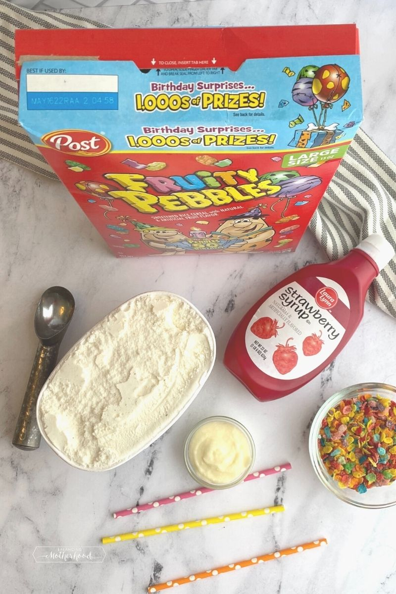 ingredients on white counter: box of Fruity Pebbles cereal, strawberry syrup, vanilla ice cream and ice cream scoop, white frosting, pink, yellow, and orange polka dot straws