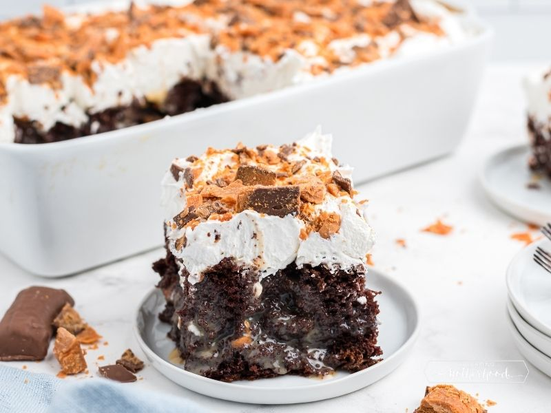 piece of poke cake on white dish with white baking dish in background