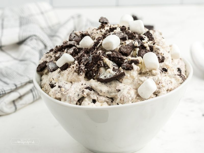 white bowl piled high with oreo fluff topped with crushed oreos and mini marshmallows