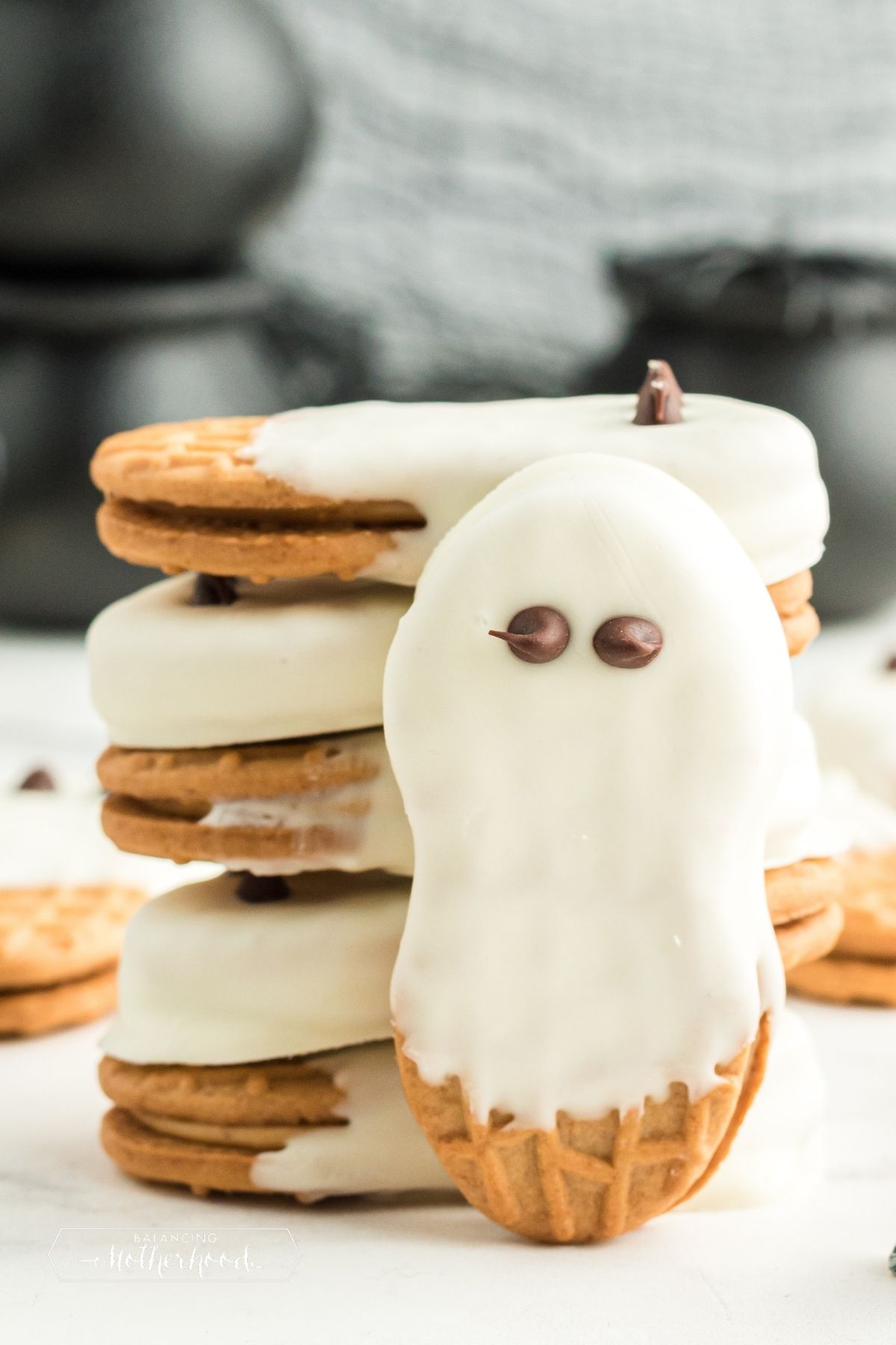 white chocolate covered Nutter Butter cookies stacked, one standing on end with chocolate eyes