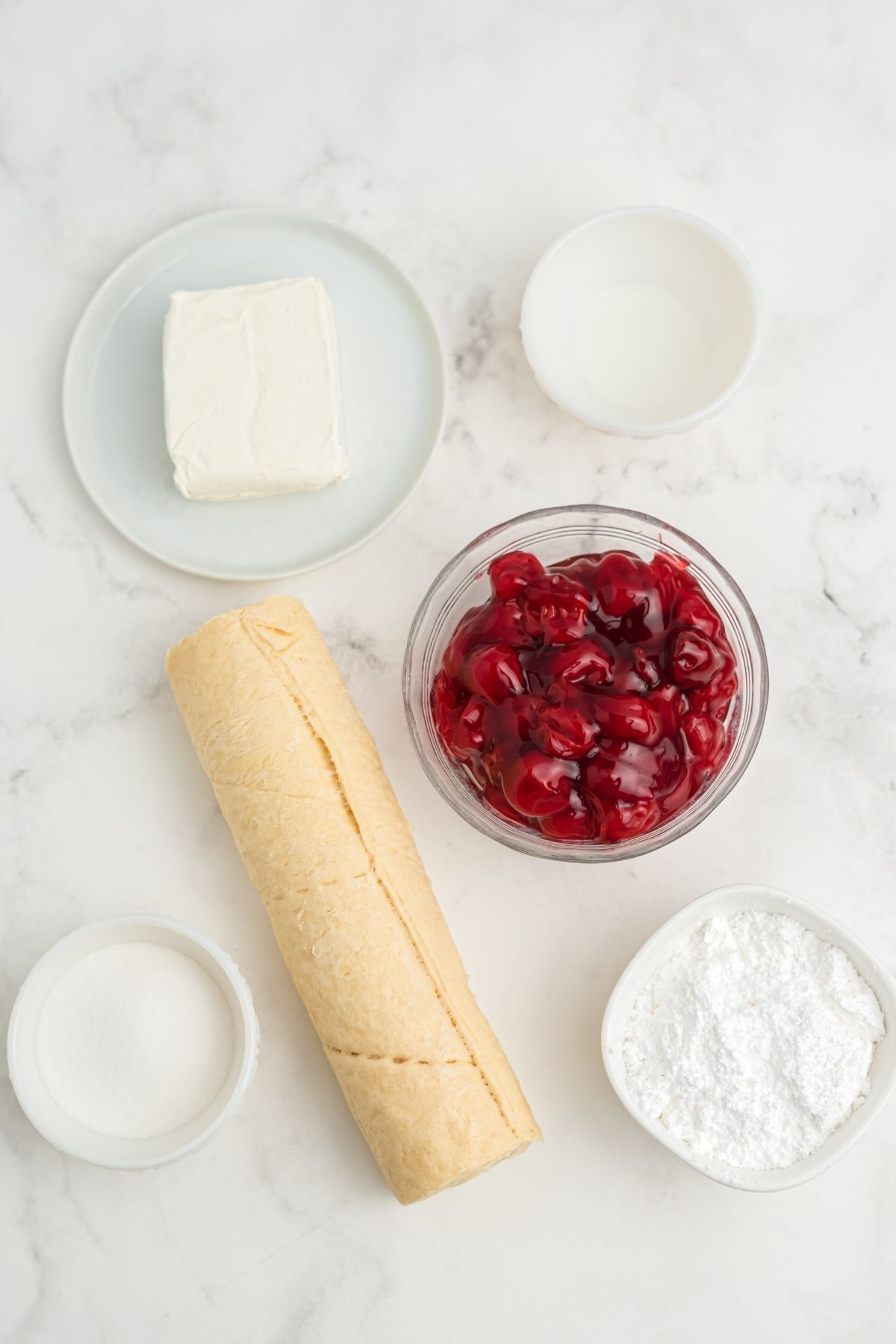 ingredients on white marble counter: block of cream cheese, milk, cherry pie filling, powdered sugar, rolled crescent roll dough, sugar