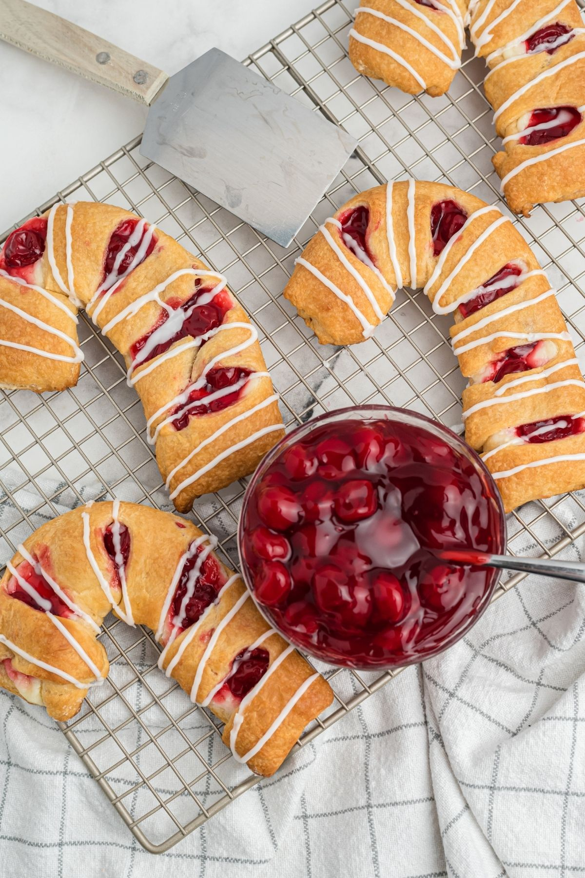 three danishes in the shape of candy canes with cherries