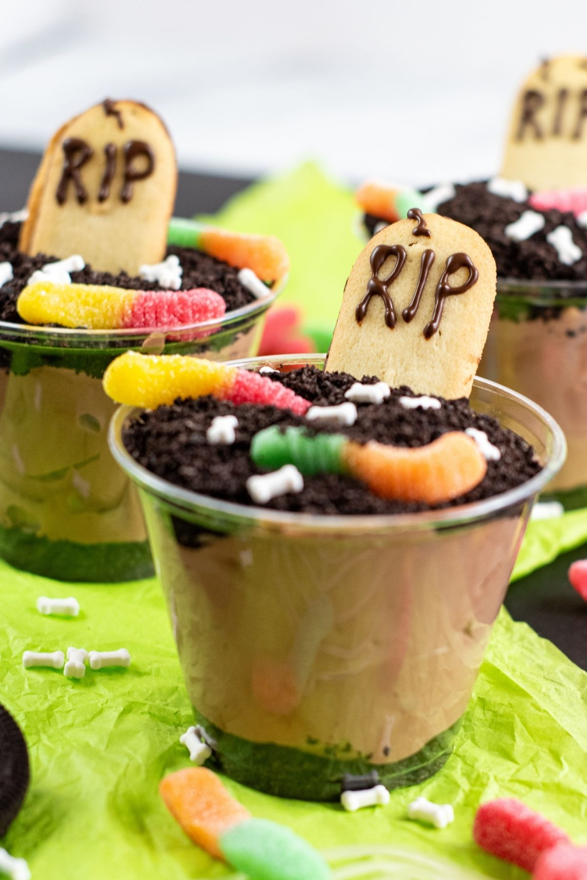 short plastic cup with chocolate pudding and crushed oreos and a RIP cookie and worms on top