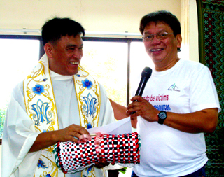 "Monsignor Elmer Abacahin, SSJV, pastor of the newly-consecrated Parish of the Holy Cross in Alubijid, Misamis Oriental, smiles as he receives a token from Balay Mindanaw Foundation, Inc. founding president Charlito ""Kaloy"" Manlupig. (Photo by BONG D. FABE)"