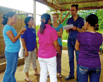 11-11-11. Hanneke van Eklik Thieme, regional office coordinator, and Kris Vanslambrouck, partner relations coordinator, both of the Belgian group 11-11-11, talk with Sendong survivors at a camp in Barangay Indahag. (Photo by Pinky Fabe)
