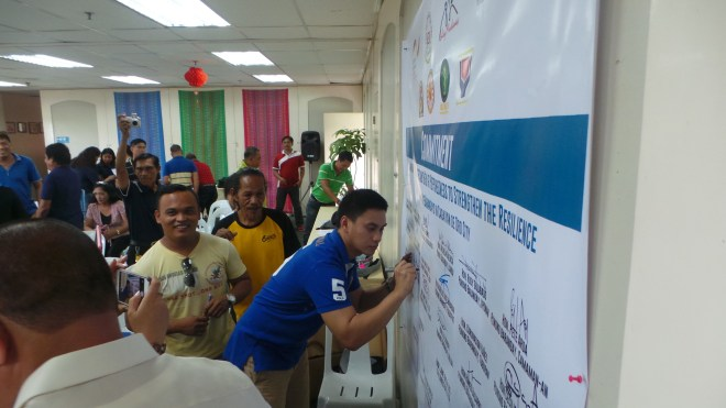Representatives from the 18 Cagayan de Oro barangays sign the symbolic commitment to the health and resiliency project supported by JUH