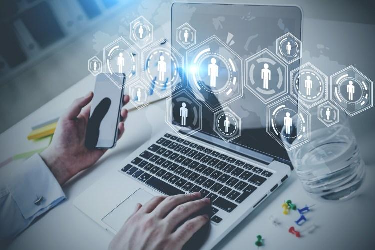 Um homem mexendo no notebook com a mão direita e na mão esquerda está segurando um smartphone, da tela do notebook aparece uns gráficos com silhueta de personas